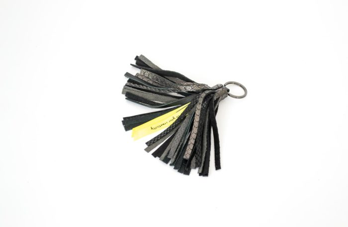 Tassel crafted with black leather in various textured finished with a golden keyring.