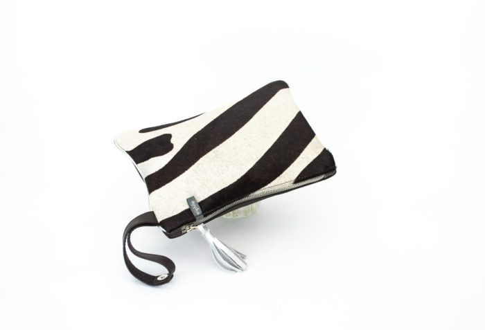 Close-up of a black and zebra print small evening bag with wrist handle.
