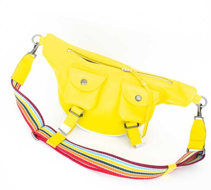 Picture of the front of the yellow travel bag with rainbow straps.